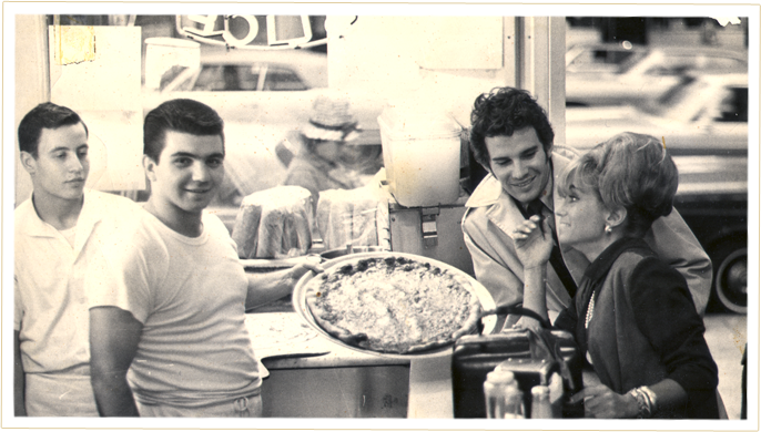 A young Nick Andrisano serving a pizza.