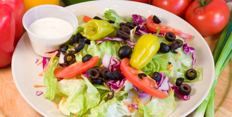 A salad with Peppers, Black Olives, carrot strips and a side of ranch dressing.