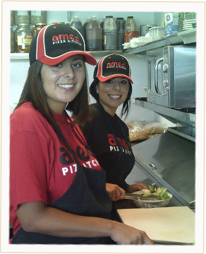 Two Team Members Making Pizzas in our World Famous Kitchen.