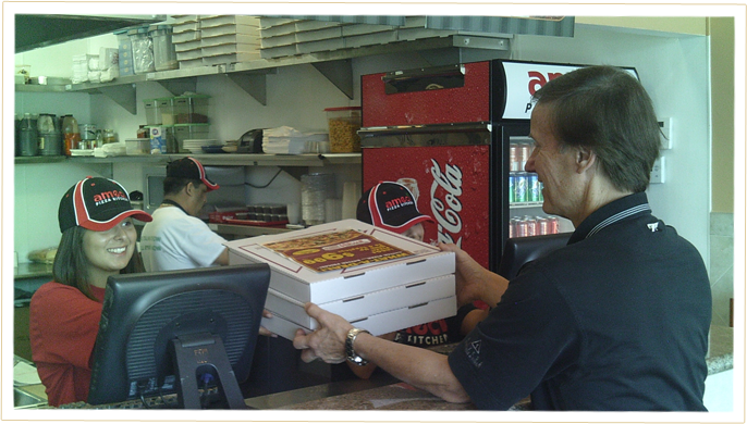 Our Ameci's Team Members Delivering 3 boxes of pizza to a happy customer.